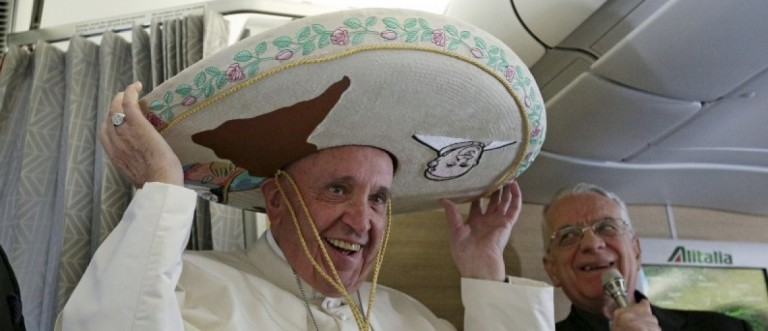 Pope Francis wears a Sombrero hat he received as a gift by a Mexican journalist aboard of the airplane to Havana, February 12, 2016. REUTERS/Alessandro Di Meo/Pool/Files