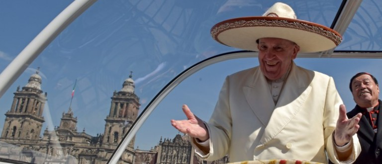 Pope Francis gestures while wearing a Mariachi hat given to him by someone in the crowd on Zocalo Square in Mexico City. REUTERS/Mexico Presidency