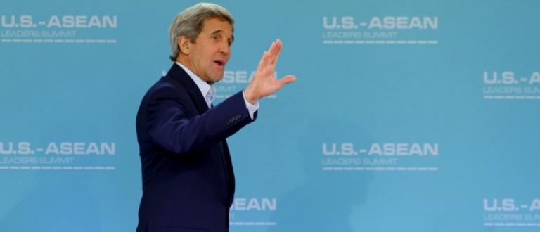 U.S. Secretary of State John Kerry waves as he arrives in a meeting room. REUTERS/Mike Blake