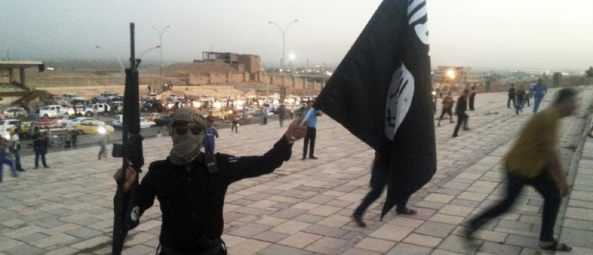 A fighter of the Islamic State of Iraq and the Levant (ISIL) holds an ISIL flag and a weapon on a street in the city of Mosul, June 23, 2014. REUTERS/Stringer/Files