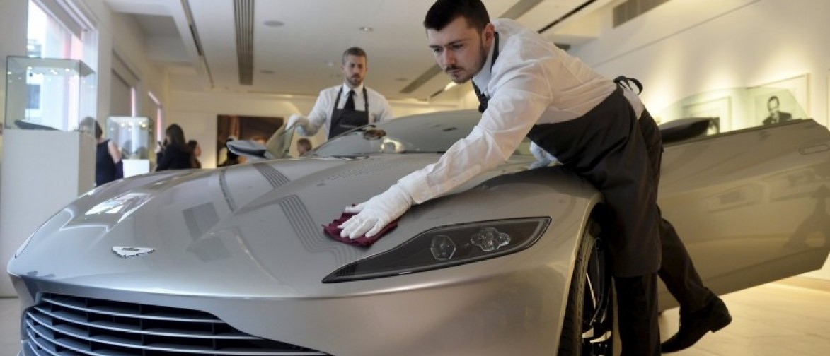 "Employees polish an Aston Martin DB10, one of the series of DB10s designed and engineered by Aston Martin for the James Bond film ""Spectre"", during a media preview of ""Spectre - the Auction"", at Christie's auction house in London February 15, 2016. REUTERS/Hannah McKay"