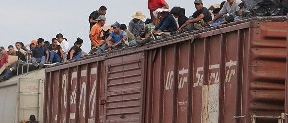 Central American immigrant get on the so-called La Bestia (The Beast) cargo train, in an attempt to reach the Mexico-US border, in Arriaga, Chiapas state, Mexico on July 16, 2014.  AFP PHOTO/ELIZABETH RUIZ        (Photo credit should read ELIZABETH RUIZ/AFP/Getty Images)
