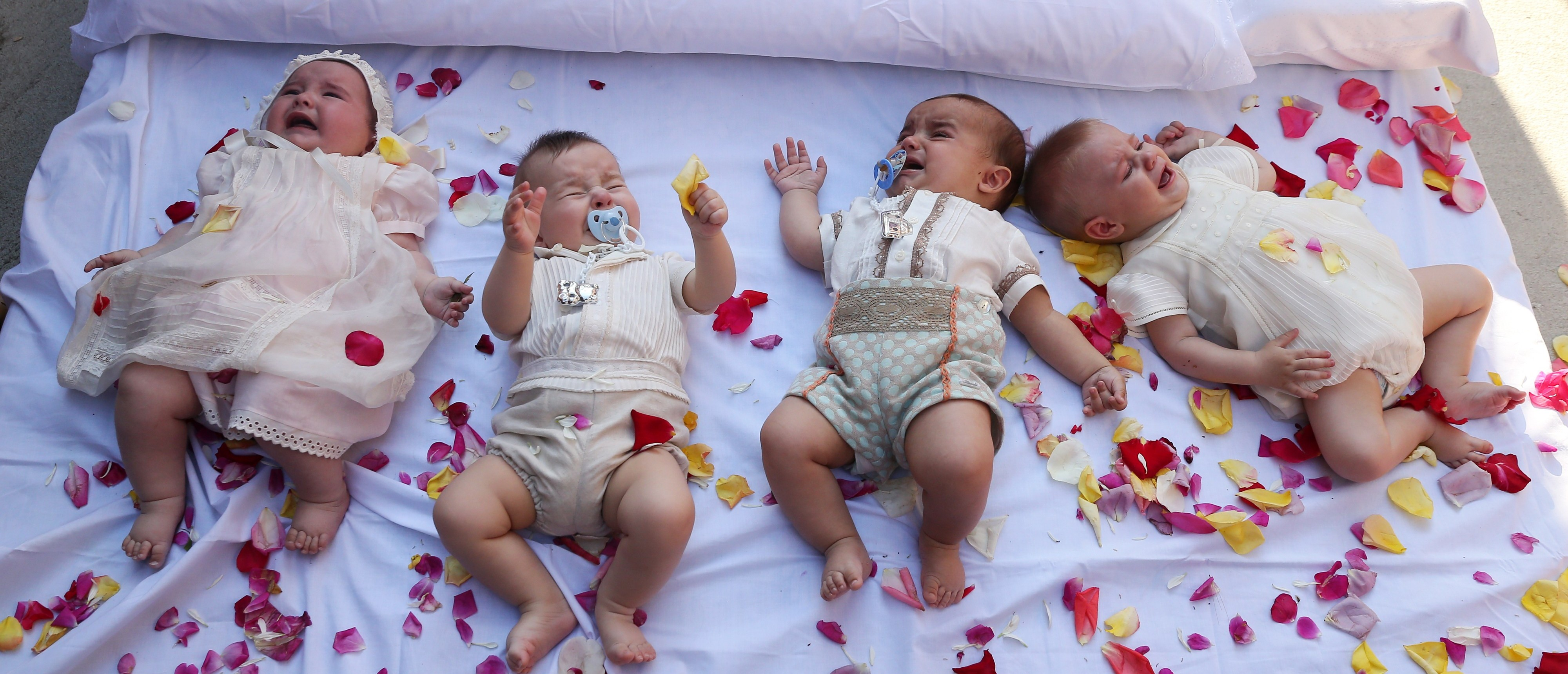 Babies react as they lie on a mattress in a street during 'El Colacho', the 'baby jumping festival' in the village of Castrillo de Murcia, near Burgos on June 7, 2015. Baby jumping (El Colacho) is a traditional Spanish practice dating back to 1620 that takes place annually to celebrate the Catholic feast of Corpus Christi. During the act - known as El Salto del Colacho (the devil's jump) or simply El Colacho - men dressed as the Devil jump over babies born in the last twelve months of the year who lie on mattresses in the street. CESAR MANSO/AFP/Getty Images)