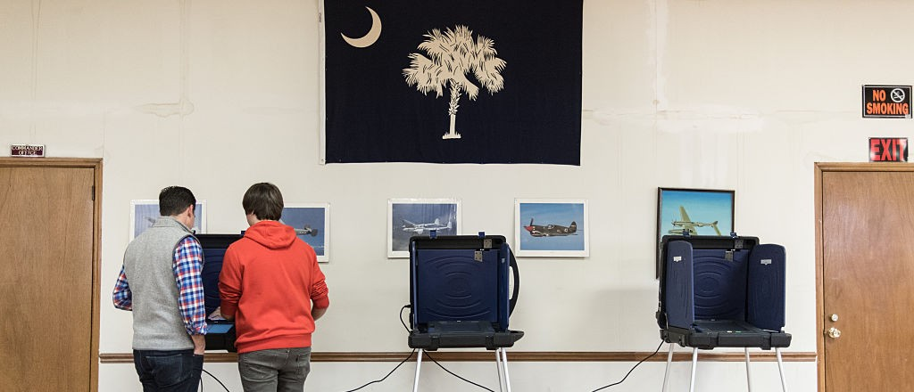 Corey Threatt, chairman of the West Columbia #3 polling station, right, assists Tim Nicholson at a voting machine for the South Carolina Republican presidential primary at American Legion Post 79 on February 20, 2016 in West Columbia, South Carolina. (Photo by Sean Rayford/Getty Images)