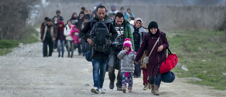 Migrants and refugees from Syria and Iraq cross the Greek-Macedonian border near the town of Gevgelija on February 23, 2016. (ROBERT ATANASOVSKI/AFP/Getty Images)