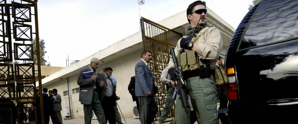 A foreign security contractor stands guard to allow Iraqi election officials and US embassy officials to exit a meeting to address local concerns over the upcoming elections, in Mosul, Iraq, 27 November, 2005. A total of 228 political parties or individual candidates are running for election in the December 15 poll, the final step in the political transition to democracy following the toppling of dictator Saddam Hussein in April 2003. (DAVID FURST/AFP/Getty Images)