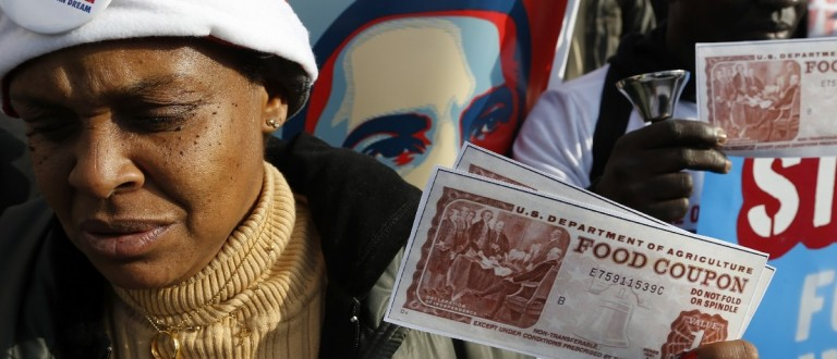 Protesters hold replicas of food stamps (REUTERS/Jonathan Ernst)