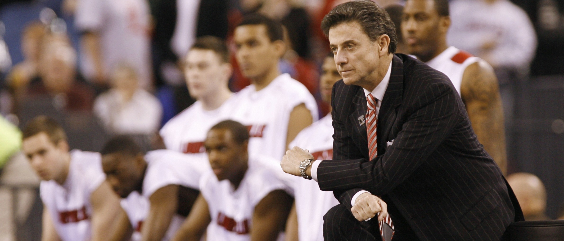 Louisville Cardinals coach Rick Pitino kneels on the sidelines as his team plays the Arizona Wildcats during the first half of their NCAA men's Midwest Regional basketball game in Indianapolis, Indiana, March 27, 2009. REUTERS/Jeff Haynes (UNITED STATES SPORT BASKETBALL) - RTXDARP