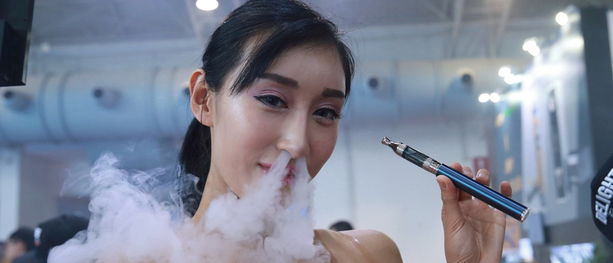 This picture taken on July 23, 2015 shows a sales staff exhaling vapour while demonstrating an electronic cigarette product at the Beijing International Vapor Distribution Alliance Expo, or the Vape China Expo, at the China International Exhibition Center in Beijing. CHINA OUT AFP PHOTO (Photo credit should read STR/AFP/Getty Images)