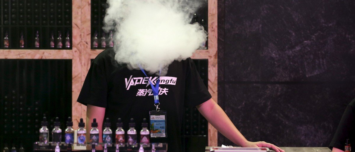 An exhibitor staff member uses an electronic cigarette at VAPE CHINA EXPO in Beijing. (REUTERS/Jason Lee)