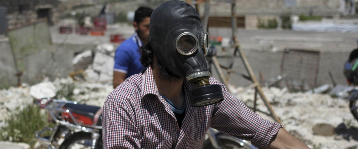 A man drives his motorcycle as he wears a gas masks after what activists said was a chlorine gas attack on Kansafra village at Idlib countryside, Syria May 7, 2015. STRINGER / Reuters