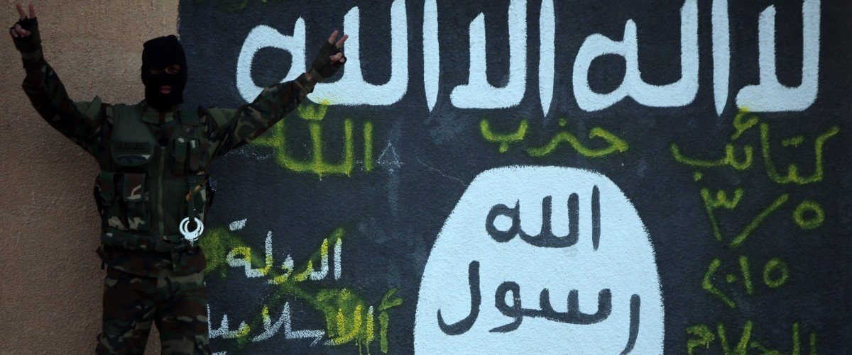 """A Shiite member of the Iraqi pro-government forces flashes the V-sign for """"victory"""" as he stands in front of a mural depicting the Islamic State (IS) group's flag on the outskirts of the Iraqi town of Ad-Dawr, on March 6, 2015, during a military operation to retake the Tikrit area from jihadists. Some 30,000 Iraqi security forces members and allied fighters launched the operation to retake Tikrit on March 2, 2015, the largest of its kind since IS overran swathes of territory last June. Ahmad al-Rubaye/AFP/Getty Images."""