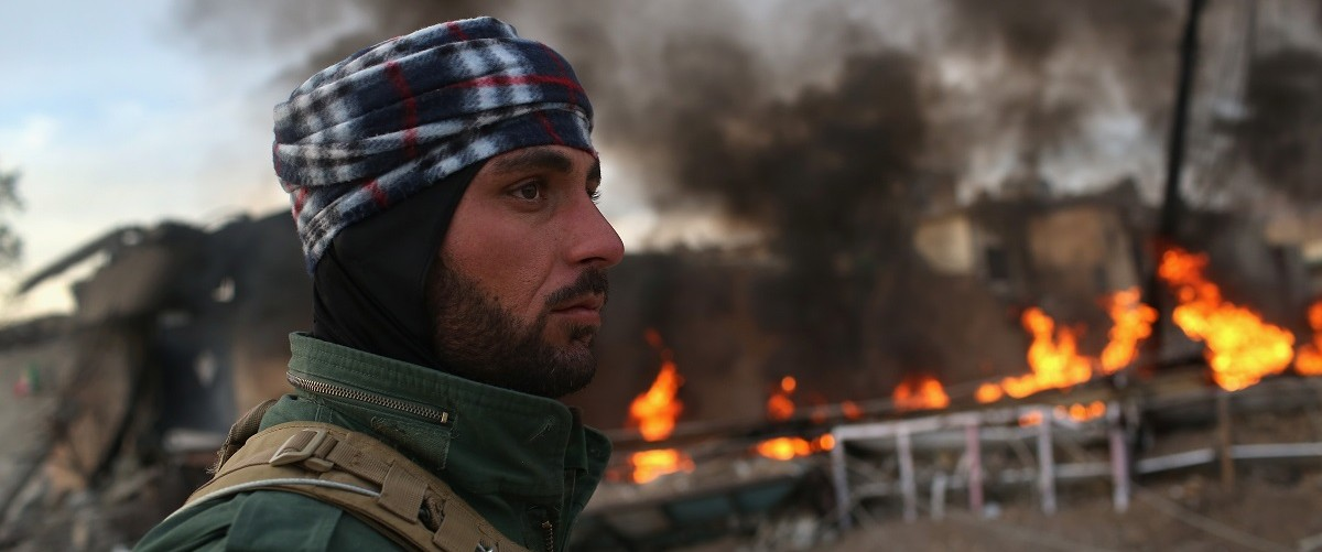 A Kurdish Peshmerga soldier passes by tires set afire days before by ISIL extremists to hinder airstrikes on November 15, 2015 in Sinjar, Iraq. Kurdish forces, with the aid of months of U.S.-led coalition airstrikes, liberated the town from ISIL extremists, known in Arabic as Daesh, in recent days. Although many minority Yazidis celebrated the victory, their home city of Sinjar lay in complete ruins. Local Yazidi fighters who fought with Kurdish forces and some former residents have been taking any salvagable items out of the rubble, the town being uninhabitable and perilously close to the frontline. (Photo by John Moore/Getty Images)