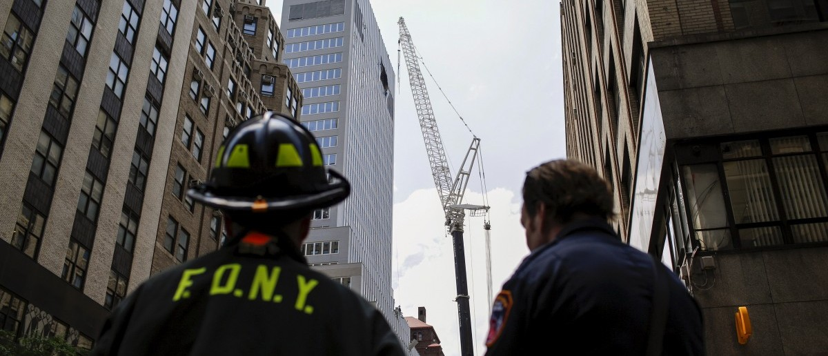 New York Fire Department members attend an emergency response after the cable of the crane snapped on a building in Manhattan, New York