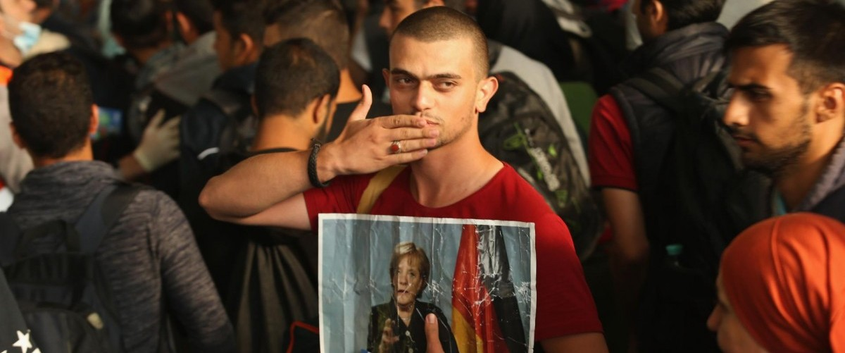 A Syrian held a picture of German Chancellor Angela Merkel as he arrived in Munich on Saturday. SEAN GALLUP/GETTY IMAGES