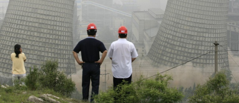 Two cooling towers are demolished at a power plant in Huaibei, east China's Anhui province June 22, 2007. China said on Thursday it was unfair for rich countries to buy its cheap goods and then condemn its greenhouse gas pollution, a day after one study suggested the nation was already the world's biggest carbon dioxide emitter. REUTERS/Stringer (CHINA)