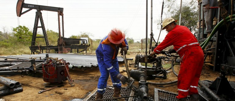 Men work at an oil pump in Lagunillas, Ciudad Ojeda, in the state of Zulia, Venezuela, March 18, 2015. Venezuela's national crime pandemic - the United Nations says the country has the world's second-highest murder rate after Honduras - is a growing headache for the oil industry, which accounts for nearly all of the country's export revenues. Hold-ups and thefts in the sector are on the rise, taking a toll on output, according to interviews with around 40 people, including oil workers, union leaders, foreign executives, opposition politicians, scrap dealers, and people who live near oil installations. To match Insight VENEZUELA-OIL/CRIME Picture taken on March 18, 2015. REUTERS/Isaac Urrutia