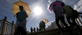 People hold their umbrellas as they walk on a bridge on a hot day at Galle Face Green in Colombo October 10, 2015. REUTERS/Dinuka Liyanawatte