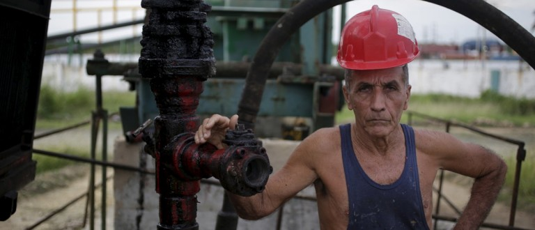 Alfredo, 69, a technician of Cuba's state-run CUPET, poses for a picture near an oil pump in Mayabeque province, Cuba, October 15, 2015. Low commodity prices, a drought at home and Venezuela's economic crisis have created a cash shortage for Cuba's Communist government, restricting its ability to trade just as it could be taking advantage of an economic opening with the United States. Picture taken october 15, 2015. REUTERS/Enrique de la Osa