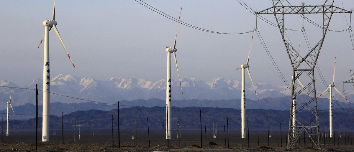 An electricity pylon is seen next to wind turbines at a wind power plant in Hami, Xinjiang Uighur Autonomous Region, China, March 21, 2015. China's wind farm firms are feeling the heat as state grid operators deliberately delay hooking them up and cut back on purchases, wasting about a fifth of the total wind power output or enough electricity to run Beijing for 40 days. Picture taken March 21, 2015.
