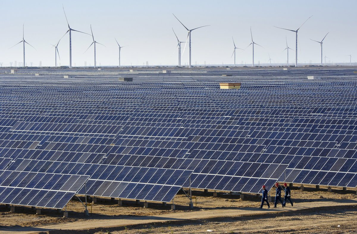 Workers walk past solar panels and wind turbines (rear) at a newly-built power plant in Hami, Xinjiang Uighur Autonomous Region, China, September 17, 2015. China