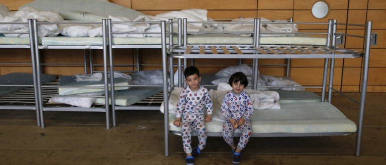Migrant children from Iraq sit on beds inside the sports hall of the Jane-Addams high school which has been transformed into a refugee shelter in Berlin's Hohenschoenhausen district, Germany, February 2, 2016 REUTERS/Fabrizio Bensch