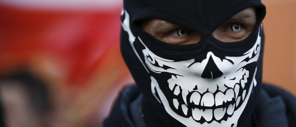 A protester wearing a mask looks on during an anti-immigrant rally in front of the Royal Castle in Warsaw, Poland February 6, 2016. REUTERS/Kacper Pempel