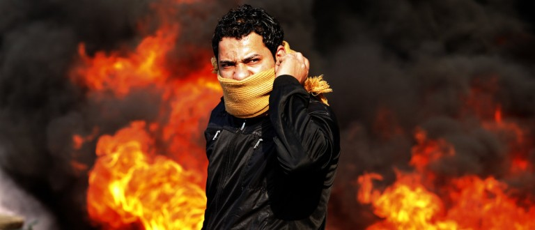 A protester stands in front of a burning barricade during a demonstration in Cairo January 28, 2011. Police and demonstrators fought running battles on the streets of Cairo on Friday in a fourth day of unprecedented protests by tens of thousands of Egyptians demanding an end to President Hosni Mubarak's three-decade rule. REUTERS/Goran Tomasevic (EGYPT - Tags: CIVIL UNREST POLITICS)