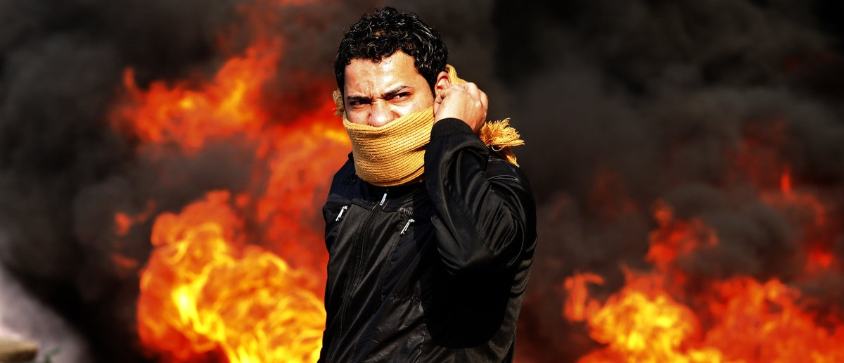 A protester stands in front of a burning barricade during a demonstration in Cairo January 28, 2011. Police and demonstrators fought running battles on the streets of Cairo on Friday in a fourth day of unprecedented protests by tens of thousands of Egyptians demanding an end to President Hosni Mubarak