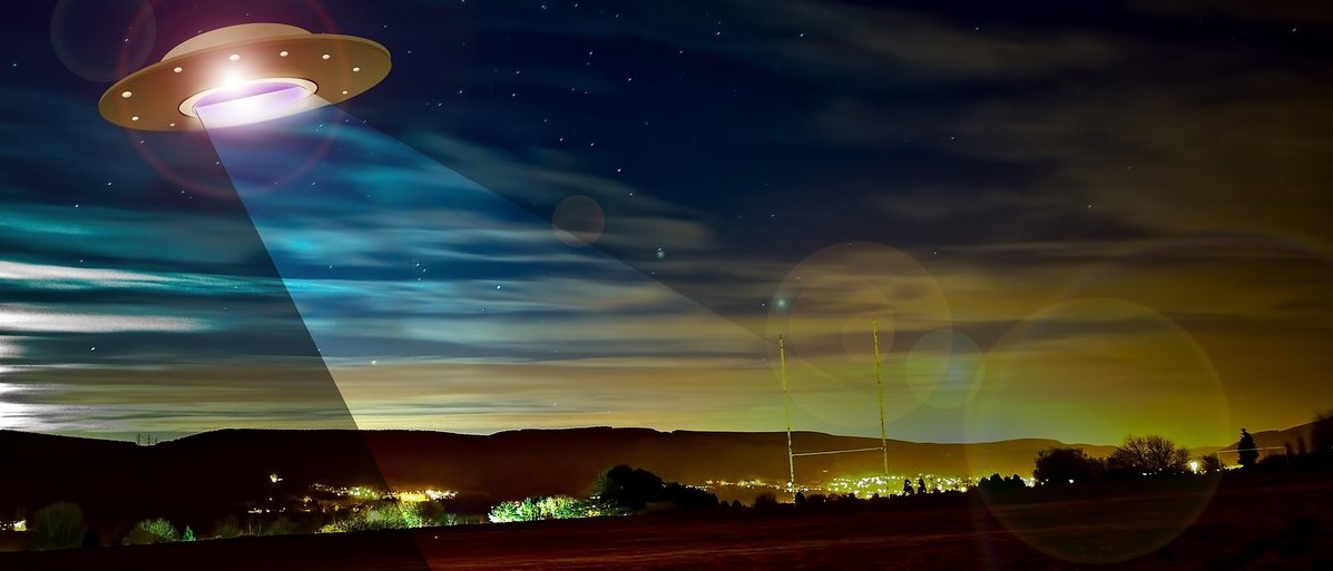 Artistic image of a UFO flying over a town. Source: Creative Commons Pixabay.com: User photovision
