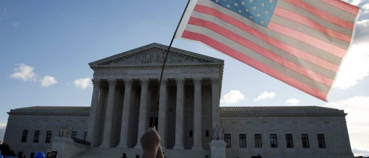 A protester holds up a flag in front of the U.S. Supreme Court on the morning the court takes up a major abortion case focusing on whether a Texas law that imposes strict regulations on abortion doctors and clinic buildings interferes with the constitutional right of a woman to end her pregnancy, in Washington March 2, 2016. REUTERS/Kevin Lamarque