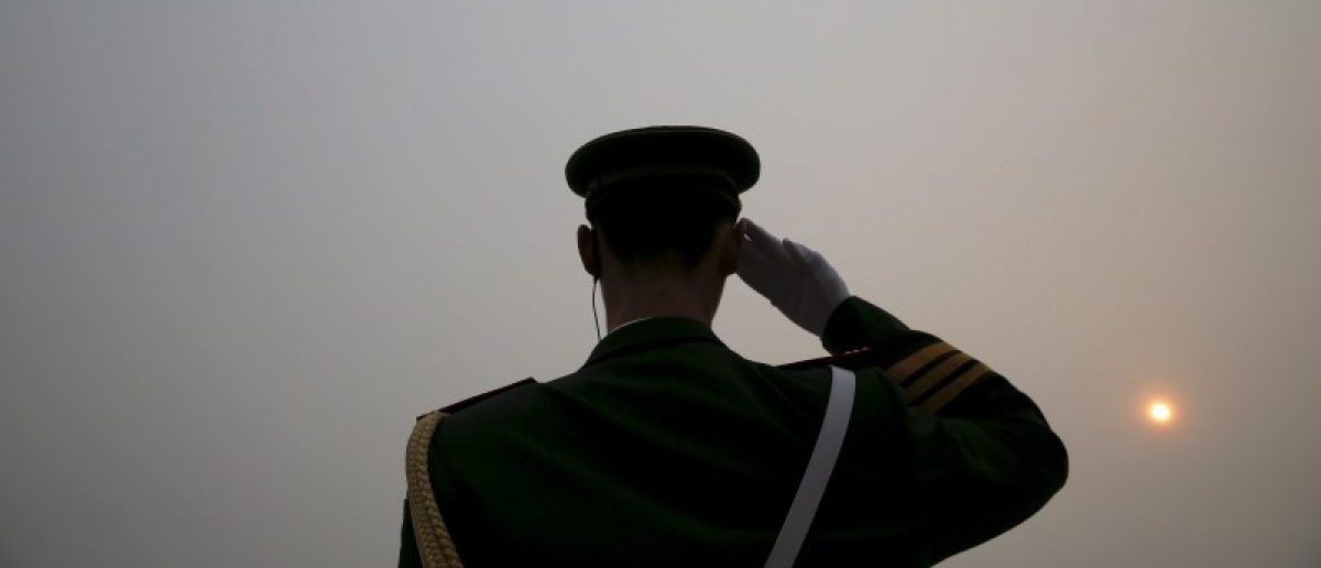 The sun is seen through smog on a severely polluted day as a paramilitary policeman salutes to delegates arriving to the Great Hall of the People ahead of Saturday's opening ceremony of the National People's Congress (NPC), in Beijing, China March 4, 2016. REUTERS/Damir Sagolj