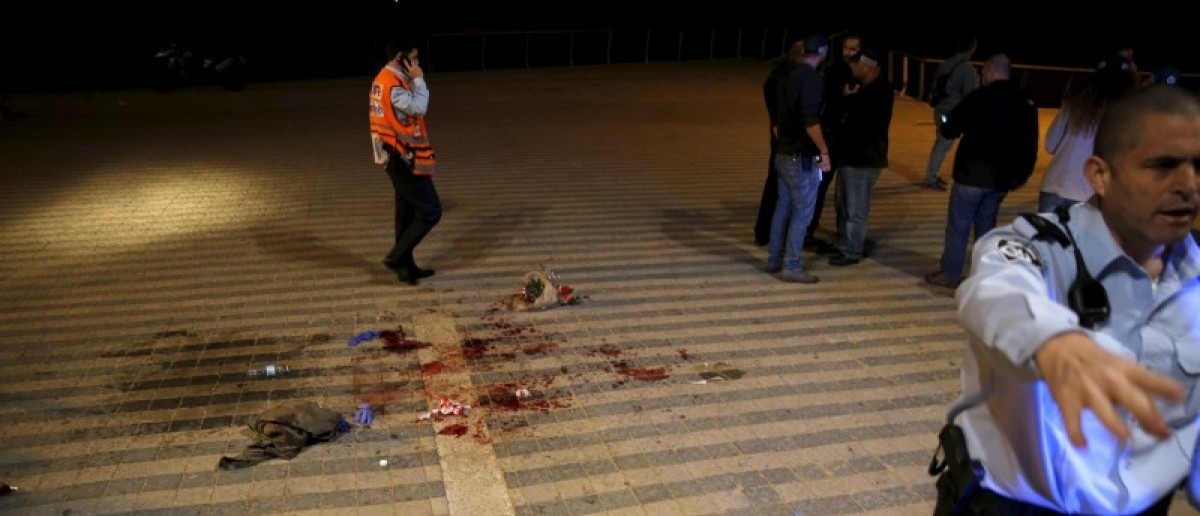 An Israeli policeman clear the spot where, according to Israeli police spoksperson, at least 10 Israelis were stabbed, in the popular Jaffa port area of Tel Aviv, Israel March 8, 2016. REUTERS/Amir Cohen