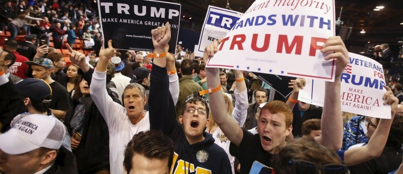 Trump supporters hold signs after Republican U.S. presidential candidate Donald Trump cancelled his rally at the University of Illinois at Chicago March 11, 2016. REUTERS/Kamil Krzaczynski