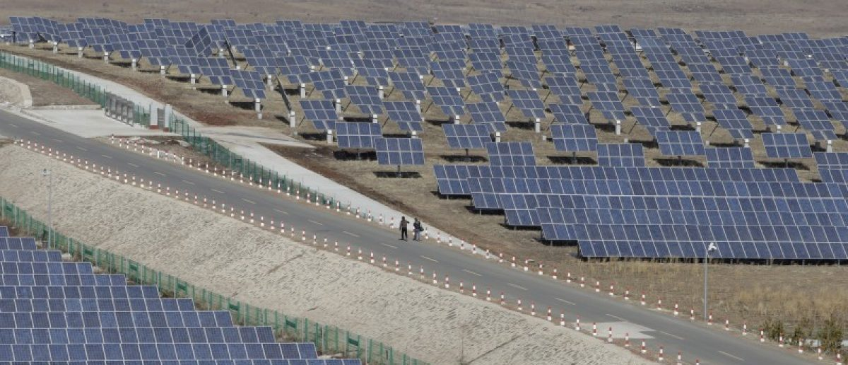 People walk past the solar panels at a wind and solar energy storage and transmission power station of State Grid Corporation of China, in Zhangjiakou of Hebei province, China, in this March 18, 2016 file picture. REUTERS/Jason Lee/Files