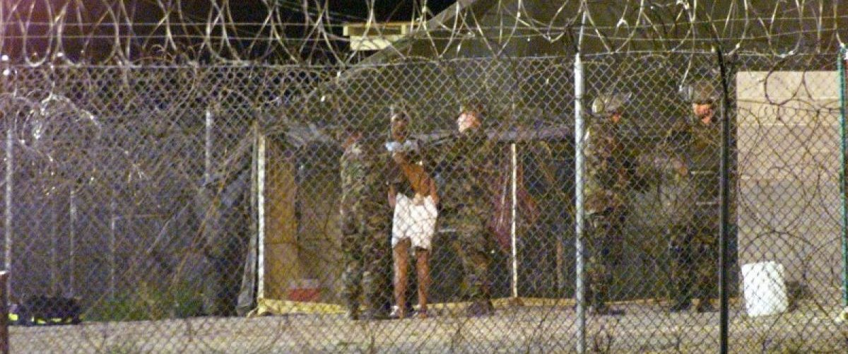 Marines at Camp X-Ray at the Naval Base at Guantanamo Bay, Cuba escort a newly arriving detainee into a processing tent after being showered in this February 7, 2002 file photo. REUTERS/Marc Serota/Files