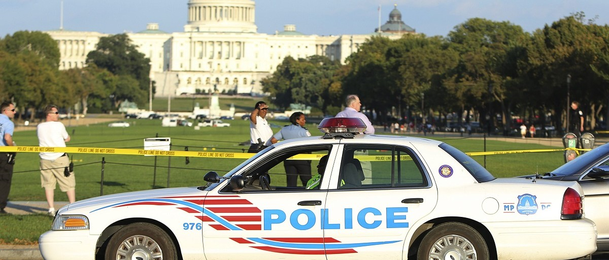 A Washington, D.C. police car arrives at the scene where a man set himself on fire near the U.S. Capitol building on the National Mall in Washington, October 4, 2013. The man was rushed to a local hospital by helicopter after using fuel to set himself ablaze near the National Gallery of Art in the middle of the mall, which remains closed due to the U.S. government shutdown. REUTERS/Gary Cameron