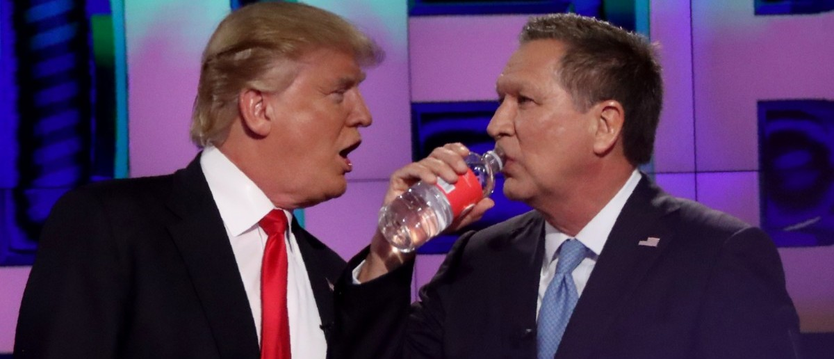 Republican presidential candidate Donald Trump talks with rival John Kasich during a commercial break in the midst of the debate sponsored by CNN at the University of Miami in Miami, March 10, 2016. (REUTERS/Carlo Allegri)