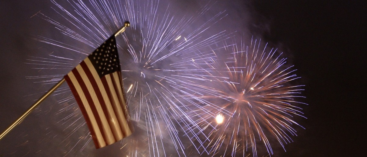 Fireworks illuminate the sky next to a U.S. national flag at the new U.S. embassy during its opening ceremony in Berlin July 4, 2008. (REUTERS/Tobias Schwarz)