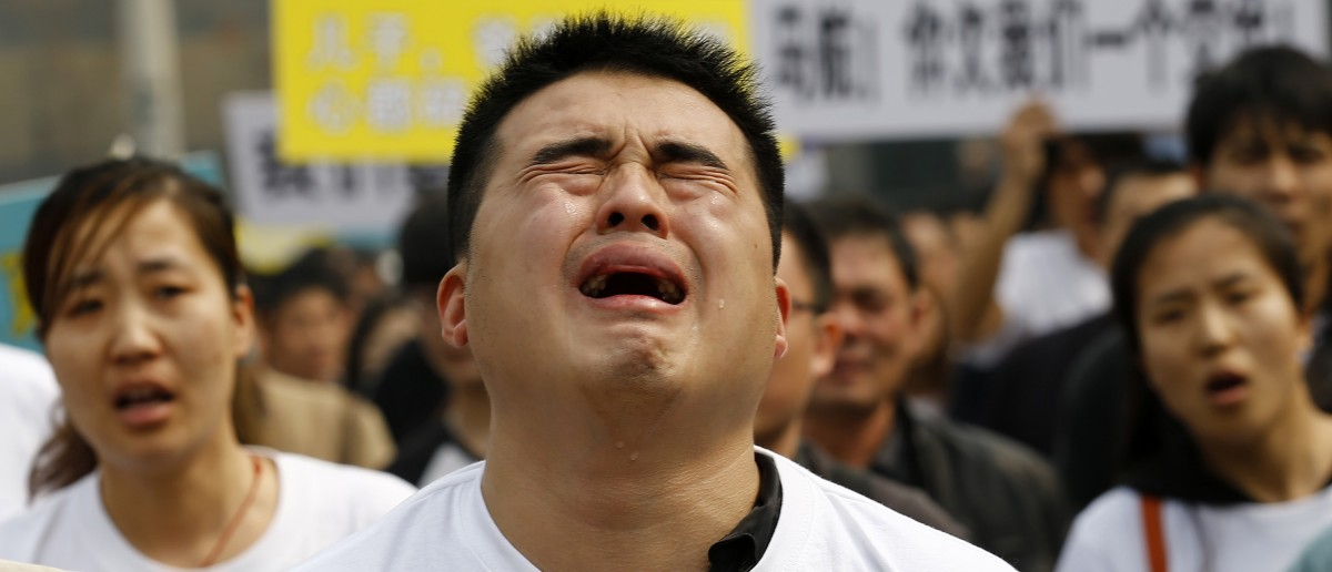 "A family member of a passenger on board Malaysia Airlines MH370 cries as he shouts slogans during a protest in front of the Malaysian embassy in Beijing, March 25, 2014. Angry relatives of Chinese passengers aboard the missing Malaysia Airlines plane denounced the Kuala Lumpur government and its national carrier as ""executioners"" on Tuesday and said they would march on the Malaysian Embassy. REUTERS/Kim Kyung-Hoon"