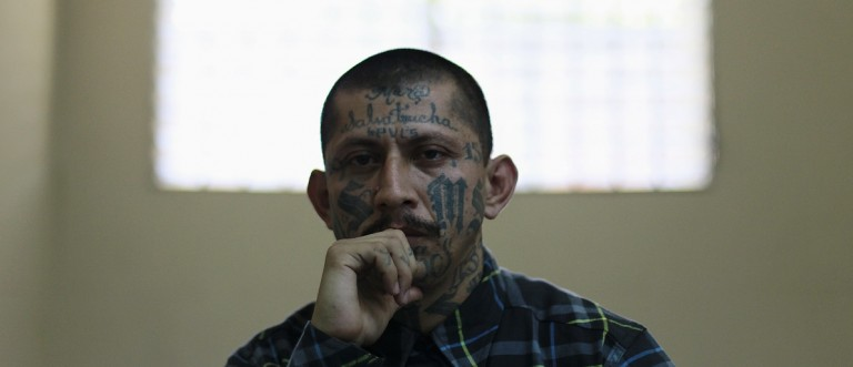 Carlos Tiberio, imprisoned leader of the Mara MS, listens during a news conference at the high security San Vicente prison in San Vicente