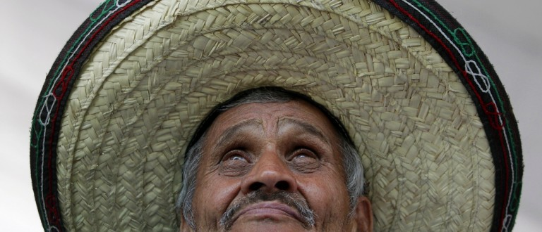 A Mexican soccer fan, wearing a sombrero, watches a large screen broadcasting the 2014 World Cup soccer match between Mexico and Cameroon, in downtown Monterrey June 13, 2014.    REUTERS/Daniel Becerril