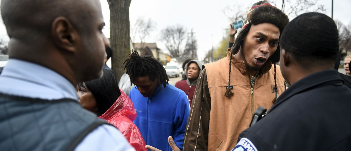 A protester argues with a police officer in front of a north Minneapolis police precinct during a protest in response of Sunday's shooting death of Jamar Clark by police officers in Minneapolis, Minnesota, November 18, 2015. State officials on Wednesday identified the two Minneapolis police officers involved in the fatal shooting of an unarmed black man that has sparked protests and dozens of arrests. REUTERS/Craig Lassig
