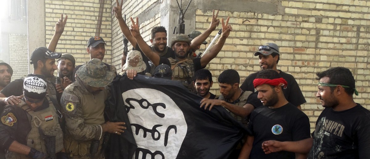 Iraqi security forces stand with an Islamist State flag which they pulled down at the University of Anbar, in Anbar province July 26, 2015. Iraqi security forces entered the University of Anbar in the western city of Ramadi on Sunday and clashed with Islamic State militants inside the compound, the joint operations command said in a statement. REUTERS/Stringer
