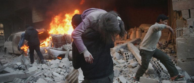 A man carries an injured child amidst rubble near a burning vehicle in a site damaged from what activists said was shelling by forces loyal to Syria's President Bashar al-Assad in the town of Douma, eastern Ghouta in Damascus, Syria December 30, 2015. REUTERS/Bassam Khabieh