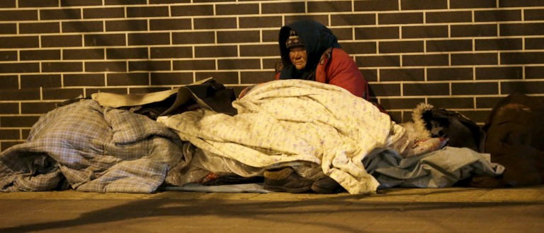 A homeless woman is seen on a cold winter. REUTERS/Jason Lee