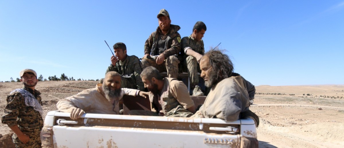 Three men that Democratic Forces of Syria fighters claimed were Islamic State fighters sit on a pick-up truck while being held as prisoners, near al-Shadadi town, Hasaka countryside, Syria, February 18, 2016.  REUTERS/Rodi Said