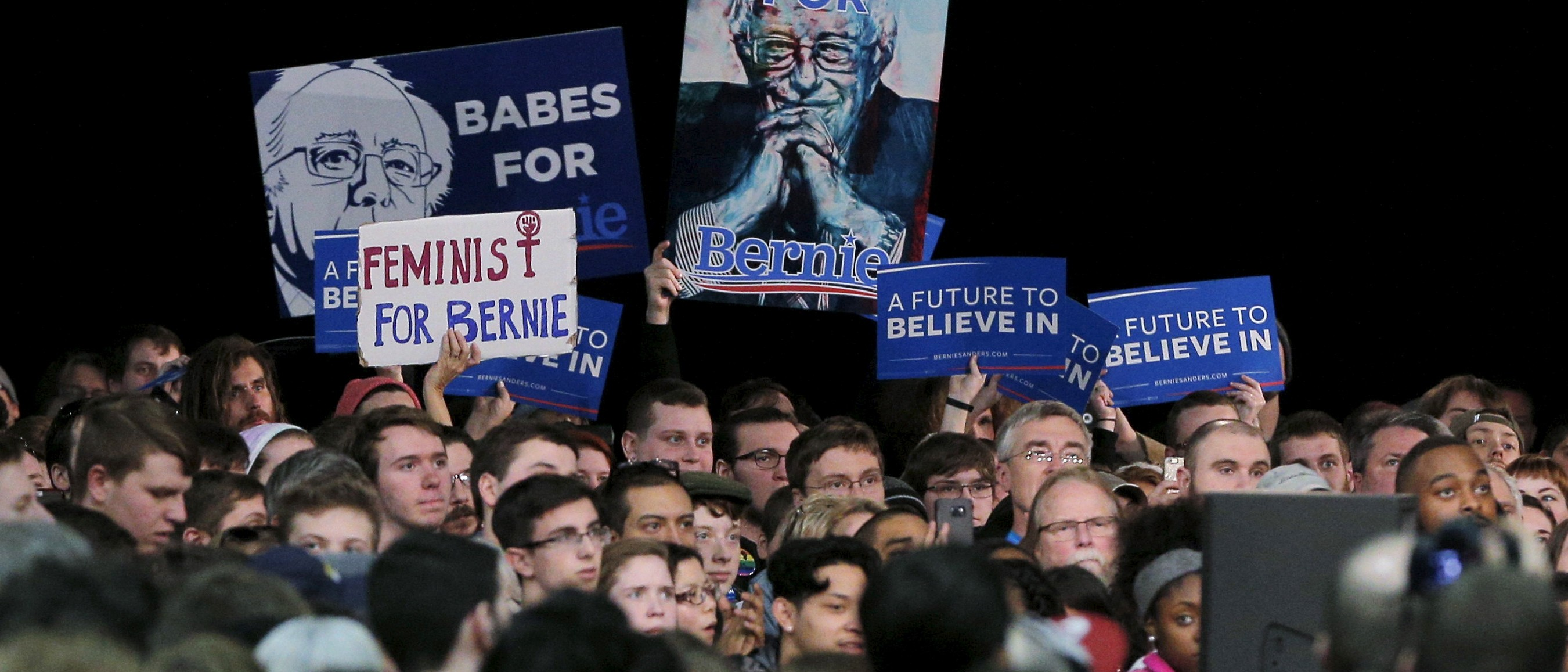 "Audience members cheer as U.S. Democratic presidential candidate and U.S. Senator Bernie Sanders speaks a campaign rally in Kansas City, Missouri February 24, 2016.  Some of the signs in the audience read ""Feminist for Bernie"" and ""Babes for Bernie.""  REUTERS/Brian Snyder"