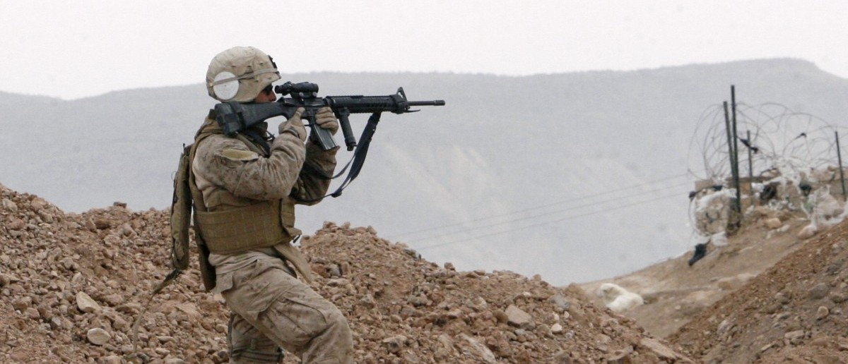 A U.S. Marine of Mobile Assault Company, 1st Battalion looks through the scope of his rifle to scan an area near a polling station in Sinjar, 390 km (240 miles) northwest of of Baghdad January 31, 2009. Iraqis held their most peaceful election since the fall of Saddam Hussein on Saturday, and voting for provincial councils ended without a single major attack reported anywhere in the country. Picture taken January 31, 2009.             REUTERS/Erik de Castro