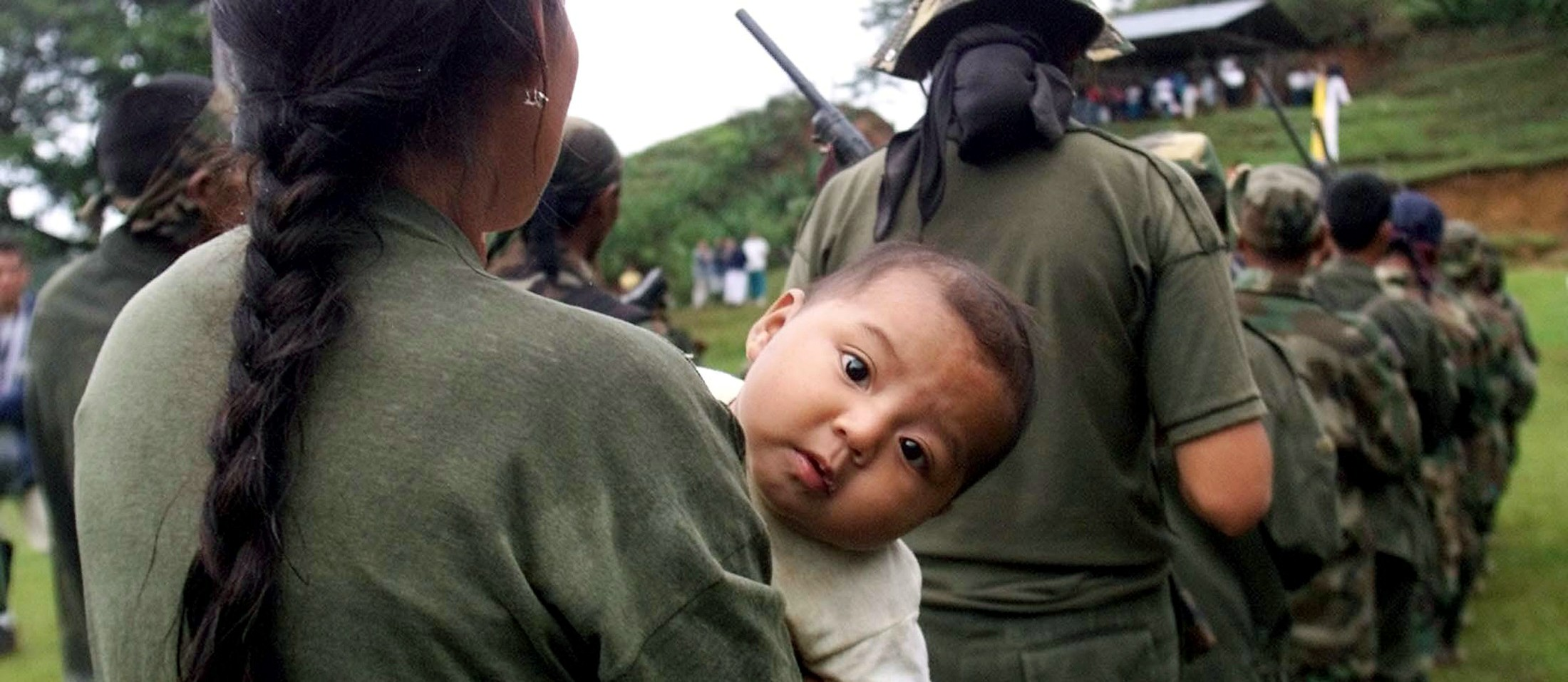 A peasant member of a self-defense group holds her baby before surrender her weapon in Ortega, Cauca province, December 6, 2003. About 150 gunmen from a little-known Colombian militia laid down their weapons on December 7, latching onto a fledgling and controversial peace plan that the government hopes will end the far-right's war against Marxist rebels.